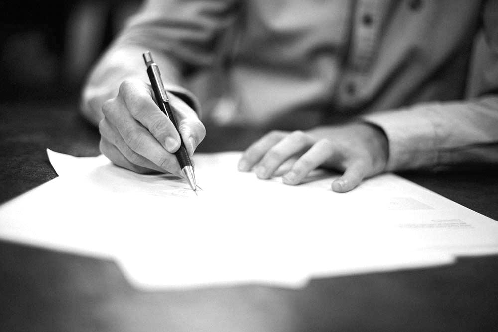 skriver med penna på papper